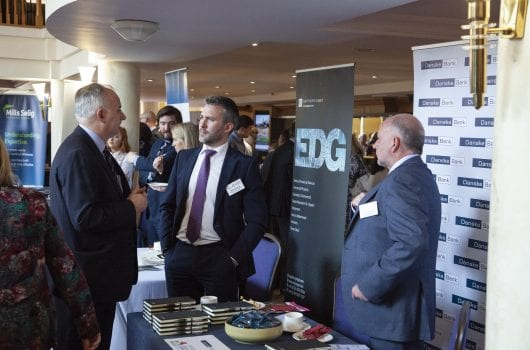 Three men in suits at Danske Bank exhibition stand at a NIFHA conference