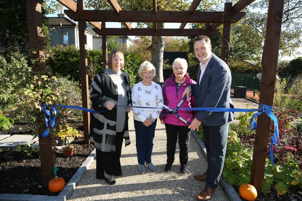 A man in a suit cutting a ribbon in a garden as four women look on