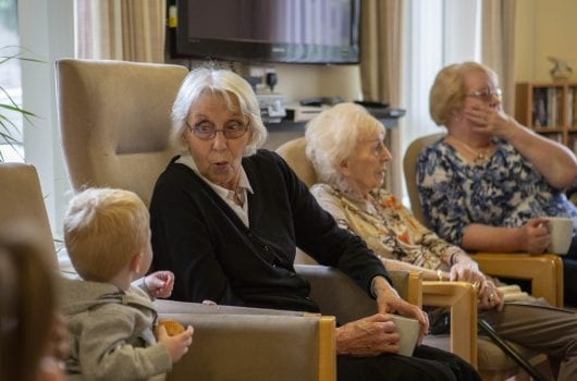 Elderly ladies enjoy spending time with infants and todddlers
