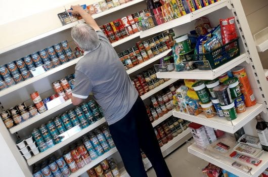 man stocking shelves at food bank