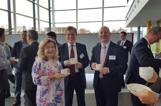 Two men and suits and a woman chatting over coffee at a business event