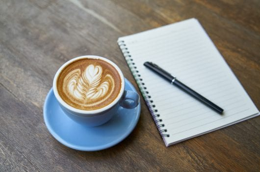 illustrative pic of coffee and notebook