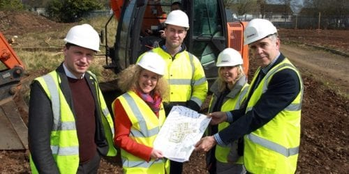 group of men and women in hard hats and hi viz vests with plans for housing development
