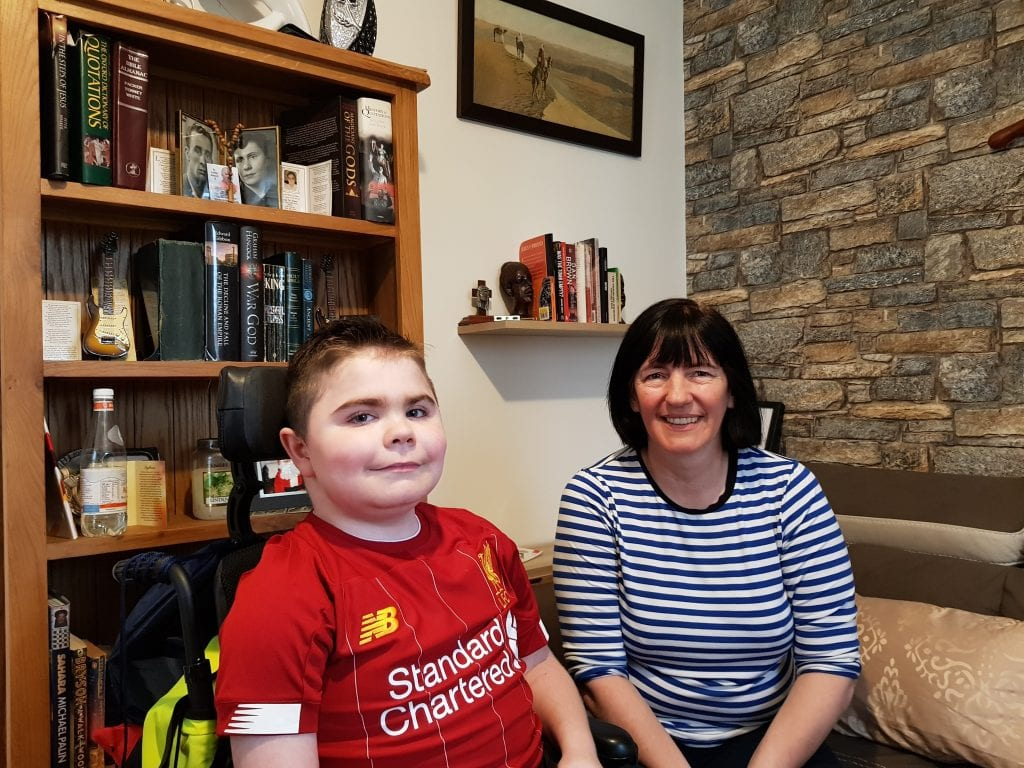 boy in wheelchair with Mum at home
