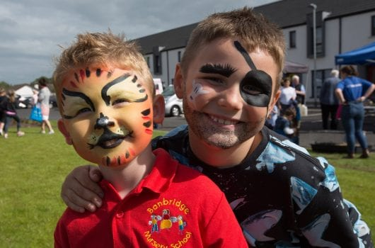 2 young boys with faces painted like tiger and pirate