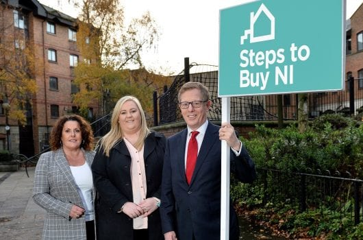 man in suit holding Steps to Buy NI sign while two women look on