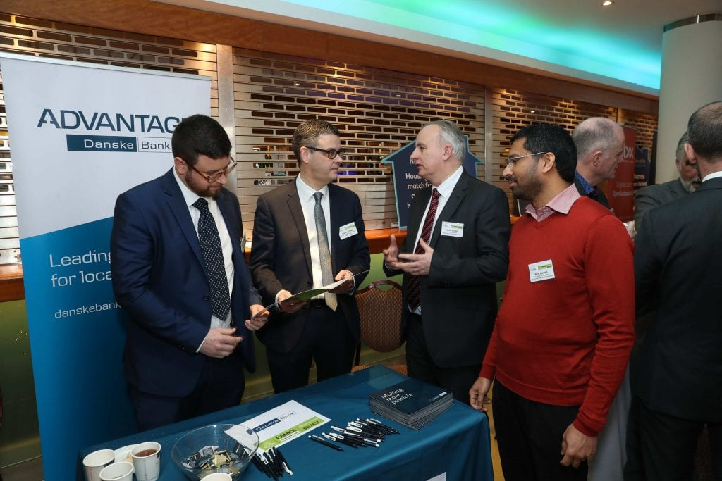 Four men at Danske Bank Corporate, Belfast, exhibition stand at a NIFHA conference