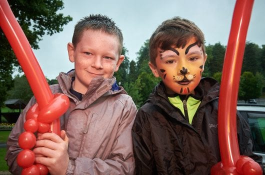 Two boys with painted faces and balloon swords