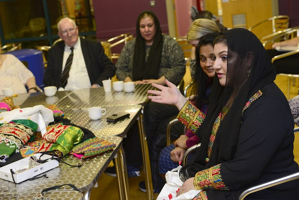 Women in Afghan traditional dress speaking to other local residents at a community event.