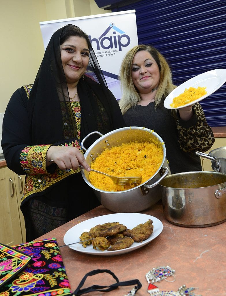 Two women, one in Afghani traditional clothing,with food and pots in kitchen