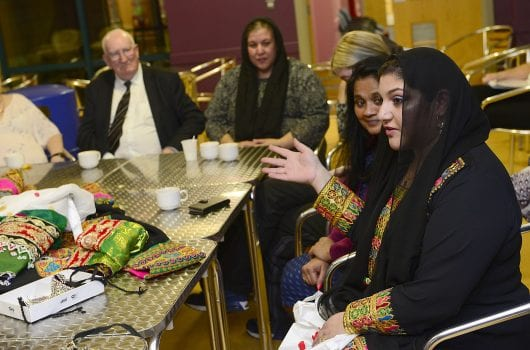 Woman in traditional Afghani clothing speaking to a group, all seated around at a table