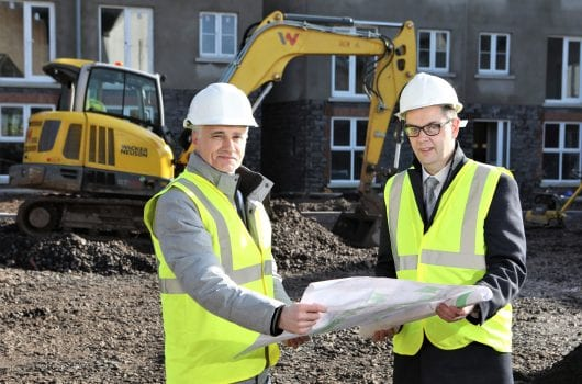 Two men in safety gear on housing development site